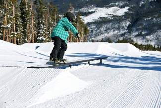 A young snowboarder nosepresses a flat box in the Incubator park at Keystone, found next to the large A51 terrain park.