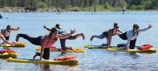 Amelia Travis of San Diego, Calif., leads a well-balanced group in stand-up paddleboard yoga Saturday morning at Lake Dillon during the second annual Season Five Summit Games.