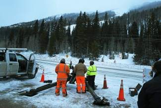 In this Feb. 21, 2014 file photo, Colorado Department of Transportation employees prepare to use an explosives launcher to try to trigger a controlled avalanche, near Empire, Colo. Two Colorado Department of Transportation workers were injured on Monday March 31, 2014, when a howitzer shell exploded prematurely while a crew was firing rounds up a hillside to clear steep chasms filled with snow and ice near Interstate 70. (AP Photo/Brennan Linsley, file)