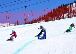 Boardercross racers in the Menehune girl's division (10-11 years old) round the first berm during qualifiers at the USASA National Championship in Copper on April 6.