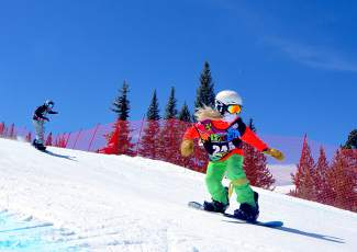 Competitors in the Grommet girl's division (10-11 years old) speed past the gates on the boardercross course at the USASA National Championships on April 6.