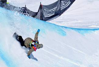 Joshua Bowman of Mammoth Lakes, California slashes on his final hit during the men's open division halfpipe qualifier at the USASA National Championships in Copper on April 7.