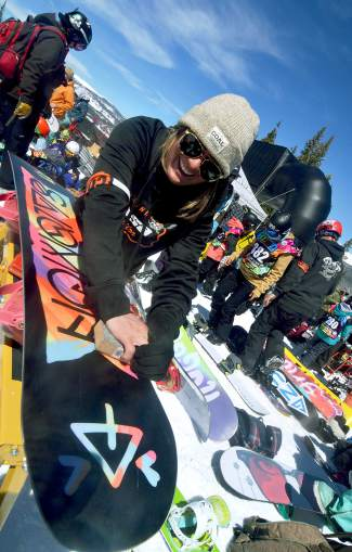 A coach gives one of her athlete's boards a final wax before the boy's and girl's youth boardercross qualifier at Copper Mountain on April 6.