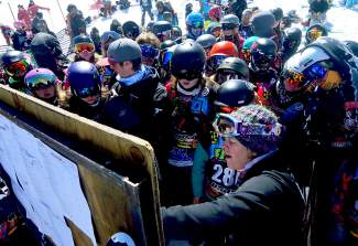 A group of athletes crowds around the start list before the boy's and girl's youth boardercross qualifier at Copper Mountain on April 6.