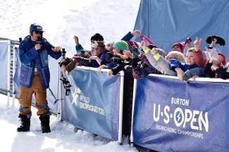 An announcer at the Burton U.S. Open entertains ski club athletes before halfpipe practice.