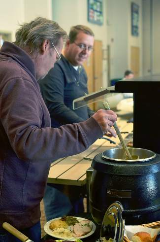From left, Bo Krupa dishes out some gravy as Jeff Harlow looks on. The Timberline group held a joint Thanksgiving dinner with the Summit Seniors on Tuesday, Nov. 24.