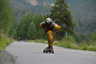 A downhill longboarder tucks for speed on a rec path straightaway about 4 miles from the top of Vail Pass.