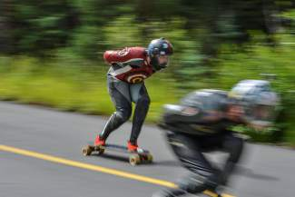 Two downhill longboarders jockey for position while bombing down the western side of Vail Pass.