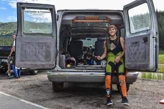 An unnamed longboarder preps for a morning of downhill riding at the top of Vail Pass.