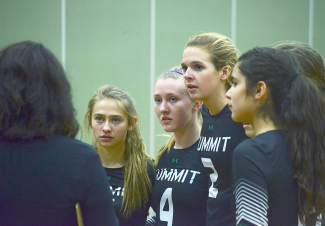 The Summit varsity volleyball team listens to head coach Liz Hughes during a timeout in the third set of a match against No. 5 Delta on Oct. 12. The Tigers lost 1-3.