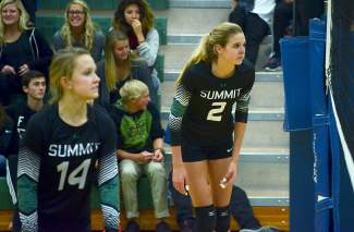 Summit's Anna Dodson (2) and Anna Mathis (14) prepare for a serve during the third set of a varsity match against No. 5 Delta on Oct. 12. The Tigers lost 1-3.