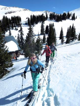 Local backcountry skiers Taryn Brooke of Breckenridge, left, Liz Clawson of Breckenridge and Brian Yohn of Frisco skin up for a afternoon run above Janet's Cabin on a recent hut trip. The hut is one of four in the Summit Huts Association system and will soon be joined by Weber Hut, a recently approved project on Baldy Mountain.