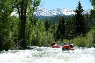 A rafting group barrels through a section of whitewater on the lower Blue River north of Silverthorne, with Red Peak and Eagle's Nest looming in the background.