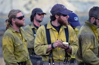 Members of the Alpine Interagency Hotshot crew listen to instructions prior to battling the Brush Creek fire on Saturday.