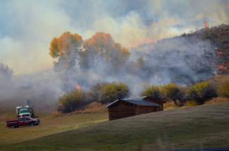 Smoke pours over the hillside behind Brush Creek Ranch on Saturday.