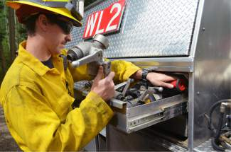 Lake Dillon Fire-Rescue firefighter Conrad Scoville replaces a hose nozzle on the accompanying wildland engine following the urban-interface training session in Frisco on Thursday, June 30.