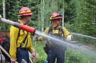 Red, White & Blue captain Keith McMillan and crew member, firefighter Brent Chapman, communicate through directing others on scene putting out parts of a wildfire during a drill at Bill's Ranch near Frisco on Tuesday, June 30.