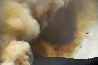 Helicopters and planes drop water and retardant on the Cold Springs Fire as it burns north east of Nederland on July 10, 2016 in Nederland, Colorado.