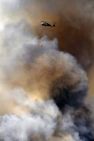 A helicopter makes water drops on the Cold Springs Fire as it continues to burn northeast of Nederland on July 10, 2016 in Nederland, Colorado. The Cold Springs fire has more than doubled in size since it began yesterday.