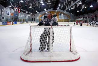 Summit goalie Wyatt Dickerson takes a break during the first period of the Tigers' game against Regis Jesuit on Jan. 18.