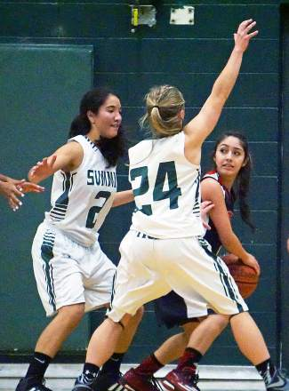 Summit's Jessica Horii (2) and Cassidy Bargell (24) defend against an Eagle Valley player during a home varsity basketball game in mid-January.