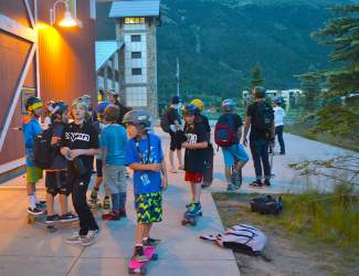 Groms get ready for a sunset longboard ride outside The Barn, home base for the Woodward Copper summer camps.