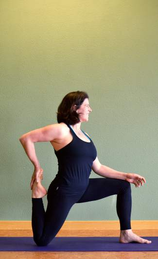 Low lunge with quad stretch yoga pose for telemark skiers.