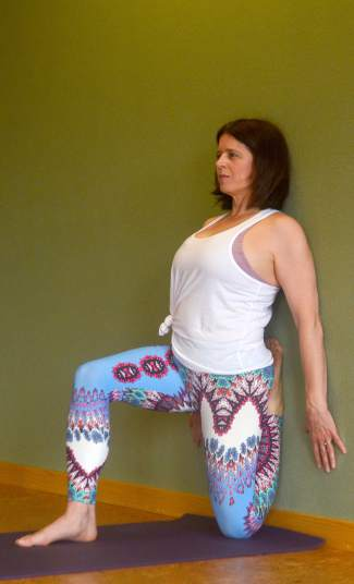 Quad stretch against a wall yoga pose for trail and road runners.