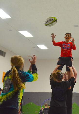 Dillon Valley Elementary students practice lineout drills with coaches from the Summit girl's rugby team during an afterschool program this May. The lineout drills were a big highlight for the kids at Dillon Valley Elementary during the CATCH rugby intro clinics.