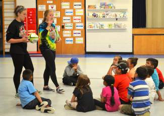 Sophomore Cassidy Bargell (right) and senior captain Natalie Gray (left) of Summit High School rugby instruct children at Dillon Valley Elementary on proper rugby technique. Almost all of the kids had no idea what rugby was prior to the clinics, which put pressure on the Summit rugby girls to coach effectively.