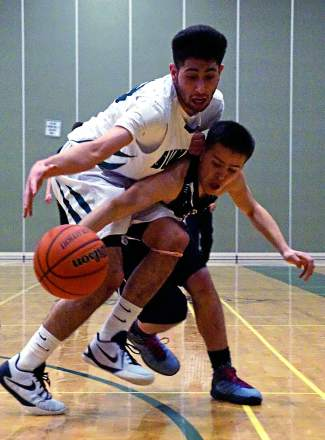 Rivals Summit and Battle Mountain go after a loose ball during the first half of a home basketball game on Jan 12. The Tigers lost, 54-72.