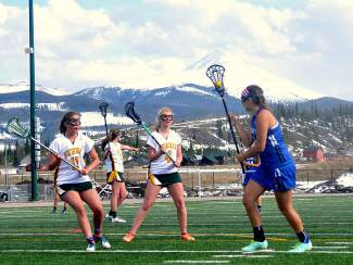 Summit lacrosse attackers Lillian Walker (11) and Elle Scott-Williams (4) box around a Fruita player during a home varsity lacrosse game on April 22. The Tigers lost, 7-12.