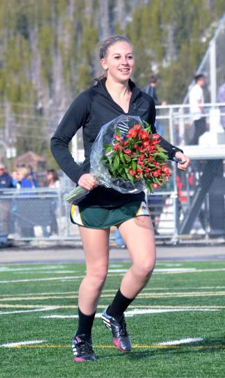 That time of year: Summit freshman Sarah Hood carries flowers across the lacrosse field after a senior asked her to prom within minutes of the final buzzer at a home varsity lacrosse game against Fruita on April 22. Hood said yes.