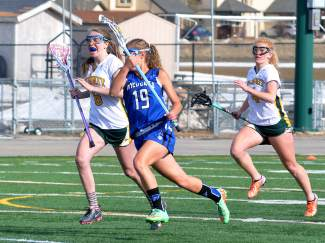 Summit's Sienna Fowles (6) and Elle Scott-Williams (4) follow a Fruita attacker at a home varsity lacrosse game on April 22. The Tigers lost, 7-12.