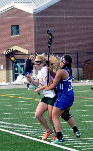 Contact first, questions later: Summit's Elle Scott-Williams (4) takes a body check from a Fruita player on the lacrosse field at Summit High in late April, captured by @sumcosports