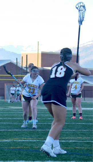 Summit's Mackenzie Hart readies for a restart while a Grand Junction player defends during the final few minutes of a girl's varsity lacrosse game on May 3. The TIgers lost at home, 7-10.