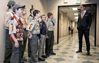 This Wednesday, April 16, 2014 photo provided by the Boy Scouts of America shows Peyton Manning talking to a group of scouts before he spoke to the Boy Scouts of America's annual breakfast in Denver. It was his first public comments since the Denver Broncos were trounced by Seattle from the opening snap of the Super Bowl. (AP Photo/Boy Scouts of America, Dan Sidor)