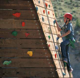 Ezekiel Martinez makes his way up the climbing wall at Roundup River Ranch, a camp for kids with serious medical conditions. Roundup River Ranch is celebrating its 10th anniversary, and will host its 4,000th camper.