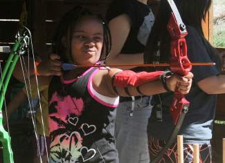 Giada Chapman takes aim during archery at Roundup River Ranch, a camp for kids with serious medical conditions.