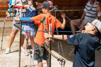 Haley Walker, Dominick Lucero and Logan Castleton take a shot at archery at Roundup River Ranch, a summer camp for kids with serious medical conditions.