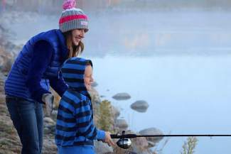 Ethan Sherman gets a quick lesson in fishing from Margaret Brammer, who's on the Shaw Regional Cancer Center staff. Brammer spends much of her vacation time as a volunteer at Roundup River Ranch.
