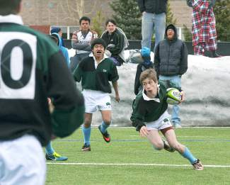 A Summit rugby player looks for a lane during the brand-new club team's first home game of the season against Palmer at Kingdom Park on March 12. The Summit crew lost, 0-74, and has yet to win a game at the halfway mark of the season.