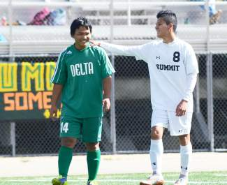 Summit junior Gerson Martinez (8) chats with a Delta defender during a pause in a varsity soccer game at home on Oct. 17. The Tigers won 1-0.
