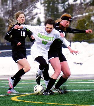 Summit's Gisele Thompson (16) tries to squeeze between a pair of Eagle Valley defenders during the Tigers' 0-0 draw at home on March 22.