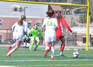 Thread the needle: Summit senior goalkeeper Lexi Vanderhoeven (green) gobbles up the ball during a home game against Glenwood Springs earlier this week, shot by @sumcosports