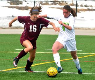 Summit defender Grace Karoly battles for the ball with Palisade's lightning-fast forward Samantha Feller in the first half of a home girl's soccer game on March 12. The Tigers lost, 0-2.