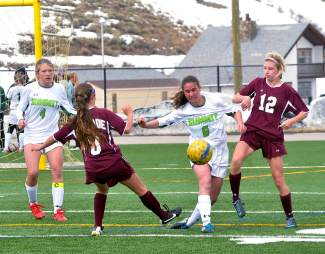 Summit's Grace Karoly (6) tries to steal the ball from two Palisade defenders in the first half of a home girl's soccer game on March 12. The Tigers lost, 0-2.