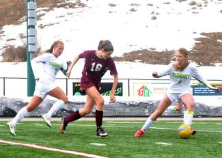 Summit defender Marin Pennell (4) and midfielder Haleigh Lecklitner (3) move to slow down Palisade's Samantha Feller in the second half of a home girl's soccer game on March 12. The Tigers lost, 0-2.