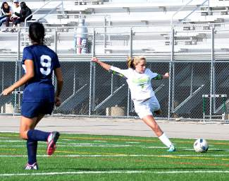 Summit sophomore Sydney Kerstiens winds up for a shot from outside the goal box during the final girl's varsity soccer game against Rifle on May 5. The Tigers won, 3-2.