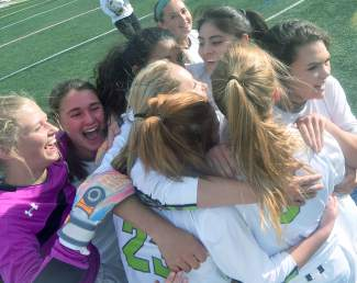 The Summit girl's soccer team celebrates after senior Katie Sullivan scored the game-winning goal in overtime of the season ender against Rifle on May 5. The Tigers won, 3-2.